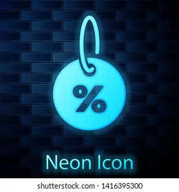 Glowing neon Discount percent tag icon isolated on brick wall background. Shopping tag sign. Special offer sign. Discount coupons symbol. Vector Illustration