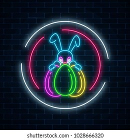 Glowing neon easter bunny with eggs sign in circle frames on dark brick wall background. Night greeting banner with easter rabbit. Vector illustration.