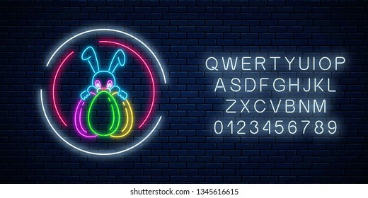 Glowing neon easter bunny with eggs sign in circle frames with alphabet on dark brick wall background. Night greeting banner with easter rabbit. Vector illustration.