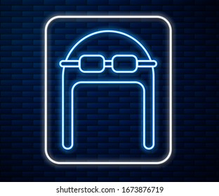 Glowing neon line Aviator hat with goggles icon isolated on brick wall background. Pilot hat.  Vector Illustration