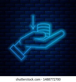 Glowing neon line Money on hand icon isolated on brick wall background. Palm holds cash with down. Cash salary decrease.  Vector Illustration