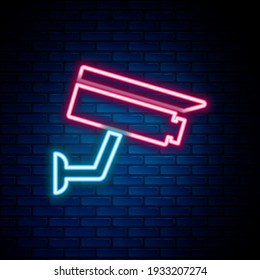 Glowing neon line Security camera icon isolated on brick wall background. Colorful outline concept. Vector