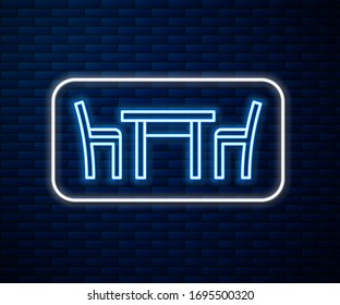 Glowing neon line Wooden table with chair icon isolated on brick wall background.  Vector Illustration