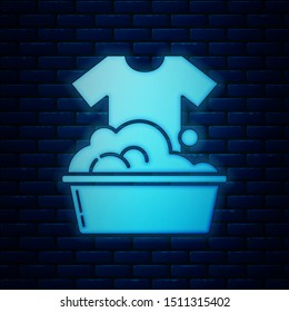 Glowing neon Plastic basin with soap suds icon isolated on brick wall background. Bowl with water. Washing clothes, cleaning equipment.  Vector Illustration