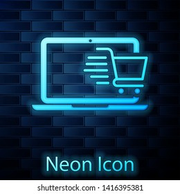 Glowing neon Shopping cart on screen laptop icon isolated on brick wall background. Concept e-commerce, e-business, online business marketing. Vector Illustration