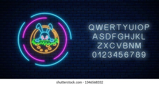 Glowing neon sign of easter bunny in basket in circle frames with alphabet on dark brick wall background. Night greeting banner with easter rabbit. Vector illustration.