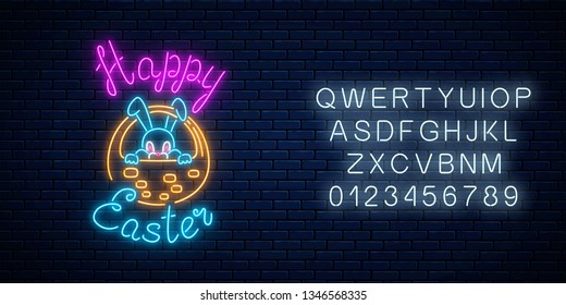 Glowing neon sign of easter bunny in basket with greeting inscription with alphabet on dark brick wall background. Night greeting banner with easter rabbit. Vector illustration.