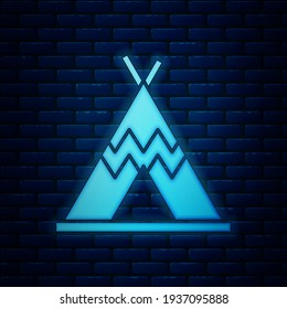 Glowing neon Traditional indian teepee or wigwam icon isolated on brick wall background. Indian tent.  Vector