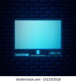 Glowing neon Video game console icon isolated on brick wall background. Game console with joystick and lcd television.  Vector Illustration