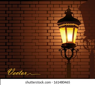 glowing street lamp against a brick wall at night