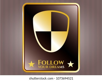 Gold emblem with shield, safety icon and Follow your dreams text inside