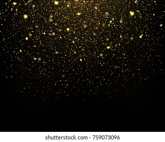 Gold glitter particles sparkles on black background.