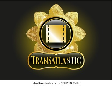 Gold shiny emblem with film icon and Transatlantic text inside