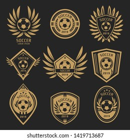 Gold soccer logo with wing style on dark background