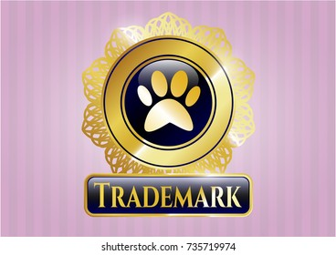Golden emblem or badge with paw icon and Trademark text inside