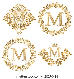 Golden letter M vintage monograms set. Heraldic coats of arms and round frames.