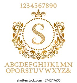 Golden patterned letters and numbers with initial monogram in coat of arms form. Shining font and elements kit for logo design.
