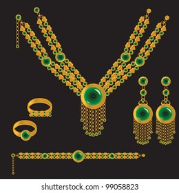 golden set from necklace rings earrings and bracelet with green stone on black background