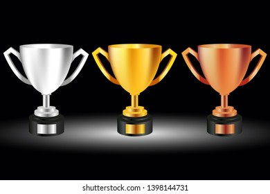 golden,silver and bronze trophies on gray background on black background