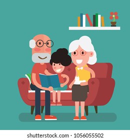 Grandparents and granddaughter  sitting in sofa and reading book