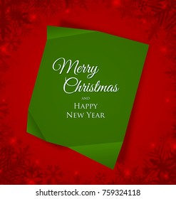 Green Merry Christmas sheet of paper placed on red background with snowflakes