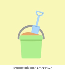 Green plastic bucket with a blue spatula that is stuck in the sand