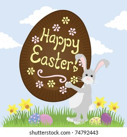 """Grey Easter Bunny carrying a huge chocolate Easter Egg with """"Happy Easter"""" iced on it."""