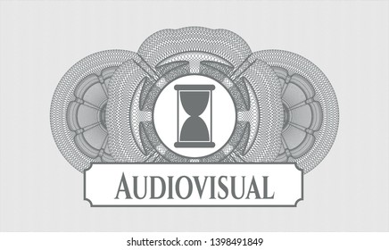 Grey rosette (money style emblem) with hourglass icon and Audiovisual text inside