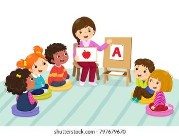 Group of preschool kids and teacher sitting on the floor.Teacher explaining alphabet to children