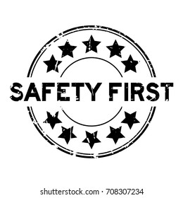 Grunge black safety first wording with star icon round rubber seal stamp on white background