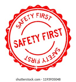 Grunge red safety first word round rubber seal stamp on white background