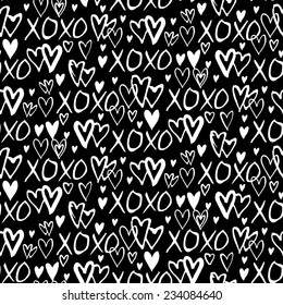 Grunge vector seamless pattern with hand painted hearts and words xoxo. Ditsy print for valentines day wrapping paper decor or wedding invitation card background in black and white colors