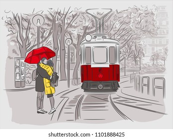 The guy and the girl are waiting for the tram under the umbrella. Cityscapes of Vienna