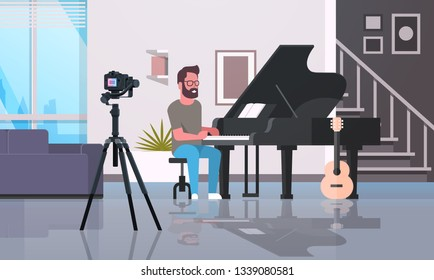 guy musical blogger recording video on camera man playing classical piano music blog concept modern apartment interior full length horizontal