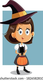 Halloween Girl in Witch Costume Going Trick or Treat. Funny child dressed for carnival holding a pumpkin candy basket