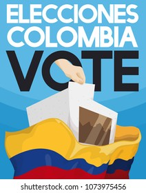 Hand depositing electoral card in voting box filled with votes, a proof of massively assistance in electoral event in Colombia (written in Spanish).
