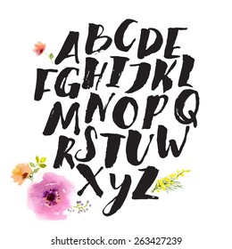 Hand drawn alphabet written with brush pen. Letters are decorated with watercolor flowers. V letter is missed here.