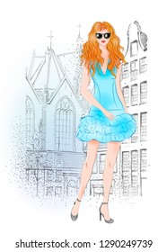 Hand drawn beautiful young woman with curly red hair on a city background. Fashion woman. Stylish cute girl in sunglasses. Sketch. Fashion illustration.  Redheaded girl in blue coctail dress.
