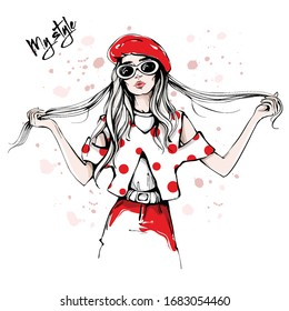 Hand drawn beautiful young woman in sunglasses and red beret. Fashion woman in spotted shirt. Stylish girl holding her long hair. Fashion woman look. Sketch. Vector illustration.