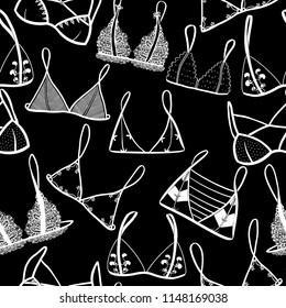 Hand drawn cute white lingerie on black background. Graphic vector seamless pattern. Lady's wardrobe. Set of lingerie, types of underwear.