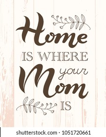 Hand drawn Home is where your Mom is typography lettering poster on wooden textured background. Text and decor around it. Rustic card, banner template. Modern classic style vector illustration.