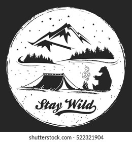 Hand drawn Inspiration and Motivation Typography for t-shirt print. Stay Wild. Travel, adventure, freedom poster with camp, tent, bear and mountains.