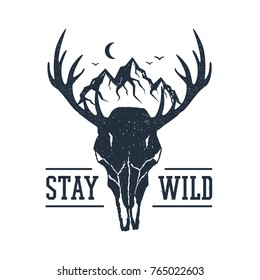 """Hand drawn inspirational label with mountains and deer skull textured vector illustrations and """"Stay wild"""" lettering."""