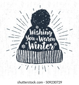 """Hand drawn label with textured winter cap vector illustration and """"Wishing you a warm winter"""" lettering."""