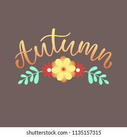 Hand drawn lettering with phrase Autumn. Isolated text on a dark brown background with flowers.