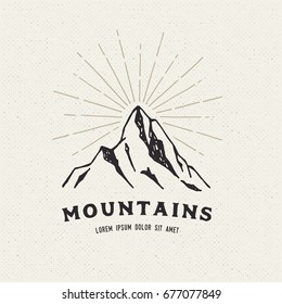 Hand Drawn mountains. Sketch illustration. Adventure logo isolated on light background. Vintage trendy label.