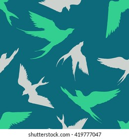 Hand drawn seamless pattern with silhouettes of  flying swallows. Endless green background