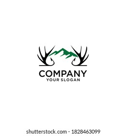 "Hand drawn travel badge with deer antlers and mountains textured vector illustration and ""Be wild and free"" inspirational lettering."
