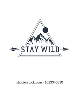 """Hand drawn travel badge with mountain peaks textured vector illustration and """"Stay wild"""" inspirational lettering."""