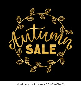 "Hand drawn typography gold lettering: ""Autumn Sale"" isolated on the black background with golden wreath."